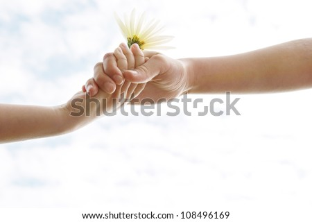 Two young girls' hands being held against the sky while holding a flower. - stock photo