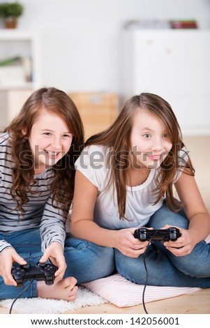 Two young girls happily playing video games in a console sitting on the living-room floor - stock photo