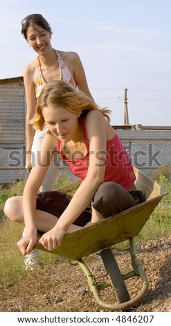 Two young girls have a good time that carry each other on a wheelbarrow intended for transportation of cargoes by one person