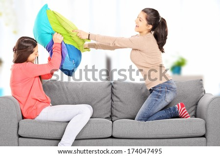 Two young girls having a pillow fight seated on sofa, at home - stock photo