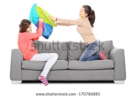Two young girls having a pillow fight seated on sofa, isolated on white background - stock photo