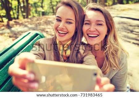 Two young girls having fun and taking photos with mobile phone. Beautiful happy women outdoors in sunny day in park autumn.
