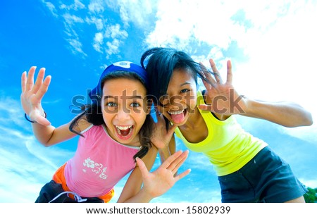Two young girls having fun making funny faces with beautiful sky background - stock photo