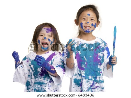Two young girls having fun painting everything. Childhood, learning, exploration family