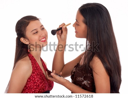 Two young girls having fun putting make up - stock photo