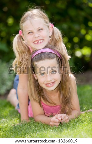 Two young girls having fun together outdoors - stock photo