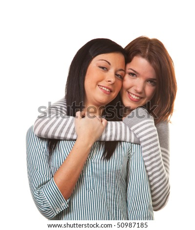 Two young girls hug each other happily and get along - stock photo