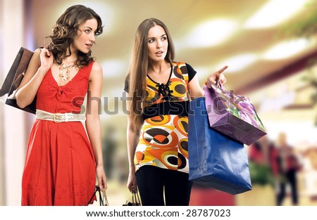 Two young girls in a shopping center - stock photo
