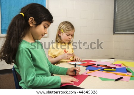 Two young girls in classroom creating art. Horizontally framed shot. - stock photo