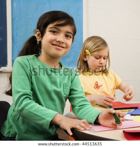 Two young girls in classroom creating art. Square format. - stock photo