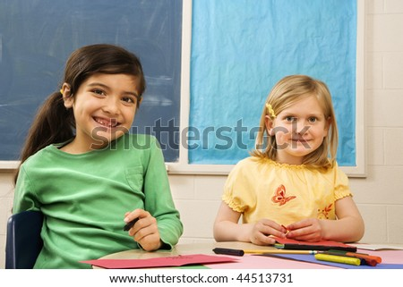Two young girls in classroom with art and drawing materials. - stock photo