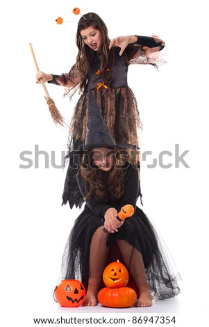 two young girls in halloween costumes holding a broom and a pumpkin - stock photo