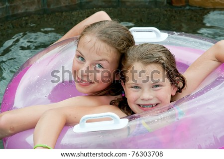 Two young girls in swimming pool with float, colors in lavender and purple - stock photo