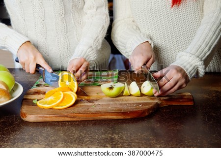 two young girls in the kitchen talking and eating fruit, healthy lifestyle, close-up - stock photo