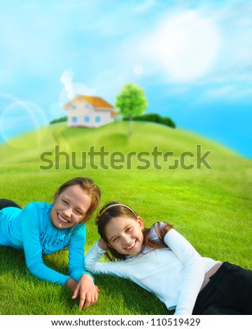Two young girls laying down on grass and smiling. Beautiful house and tree on hill