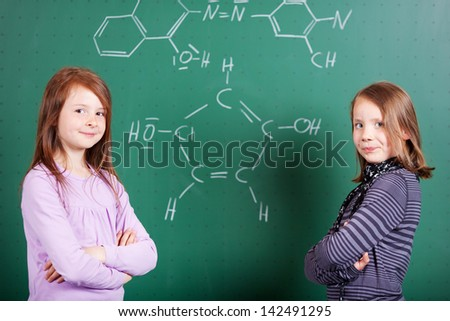 Two young girls learning chemistry standing in front of a blackboard covered in chemical formula