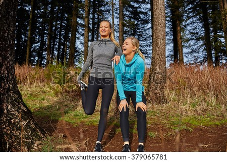 two young girls looking out during sunset stretching on each other - stock photo
