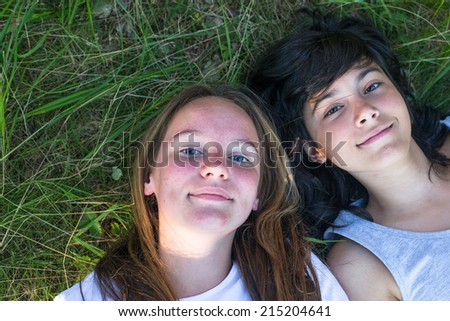 Two young girls lying on the grass, face closeup. Best friends. - stock photo