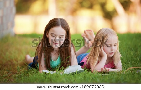 Two young girls lying on the grass outdoors reading separate books.  These siblings are enjoying time together as family during summer