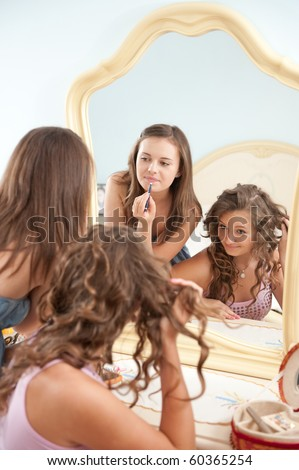 Two young girls near mirror during make-up - stock photo