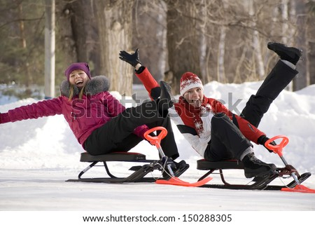 Two young girls on little snowmobiles having fun in wintry park - stock photo
