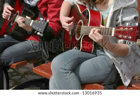 Two young girls playing acoustic guitar, real situation picture - stock photo