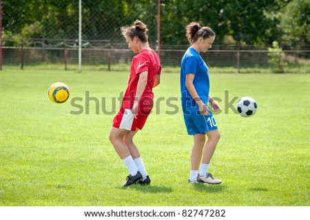Two young girls playing soccer - stock photo
