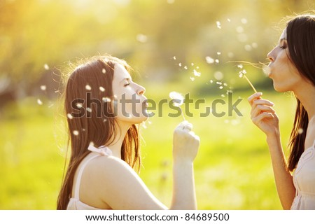 Two young girls playing with dandelions outdoor - stock photo