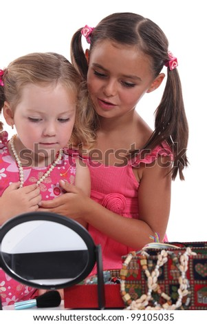 Two young girls playing with jewellery - stock photo