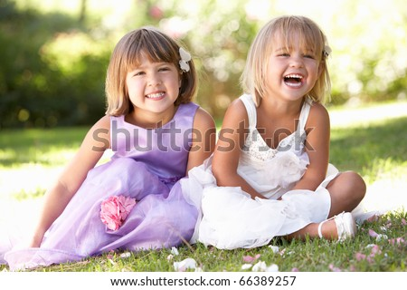 Two young girls posing in park - stock photo