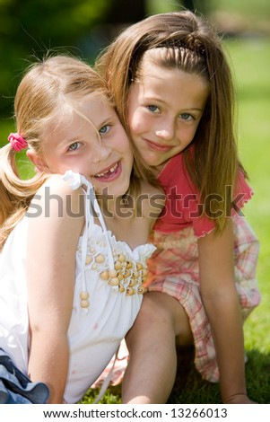 Two young girls posing together outdoors on a sunny day - stock photo