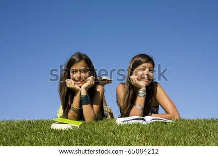 Two young girls reading books at the park - stock photo