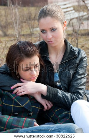 Two young girls relax on a bench in a park