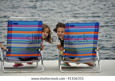two young girls relax on a dock at the lake - stock photo