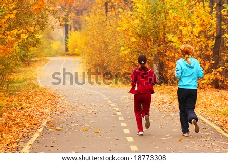 Two young girls run in the park. - stock photo