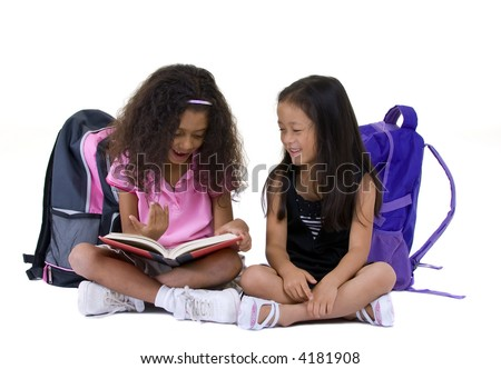 Two young girls share a book. Education, friends, ethnic, diversity. - stock photo