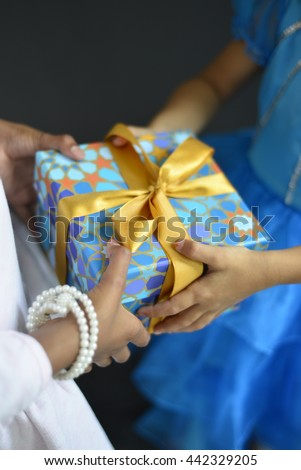 Two young girls sharing a gift. Eid and Islamic festival celebration. - stock photo