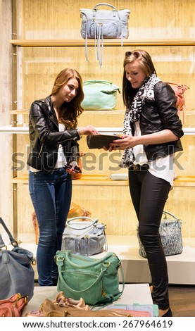 Two young girls shopping for handbags discussing in a store - stock photo