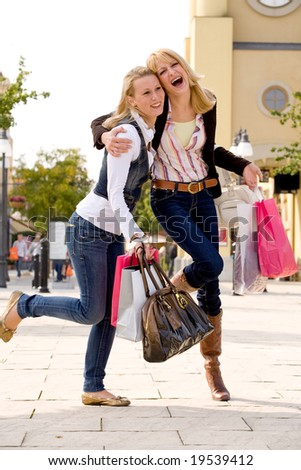 Two young girls shopping in the sunny weather - stock photo