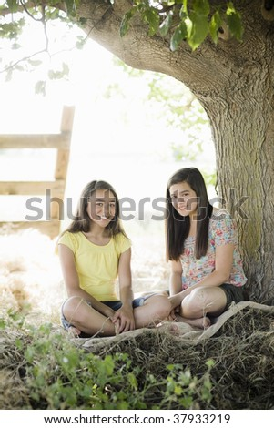 Two Young Girls Sitting on a Blanket Under a Tree - stock photo