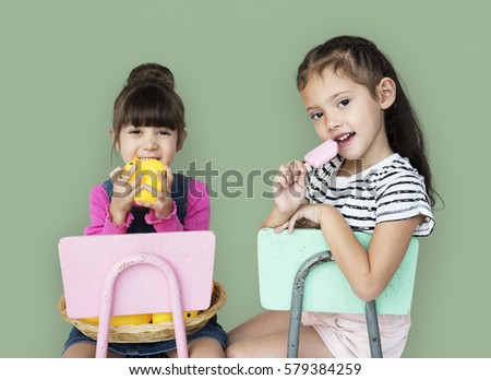 Two young girls sitting on a chair portrait