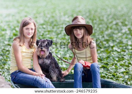Two young girls sitting on boat with their dog - stock photo
