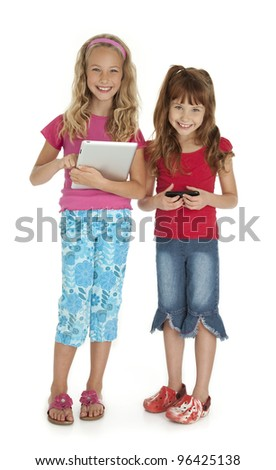 Two young girls standing,holding tablet device and smart phone on white background. - stock photo