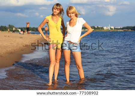 Two young girls standing in the water.