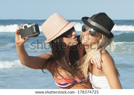 two young girls taking selfie  with film camera - stock photo