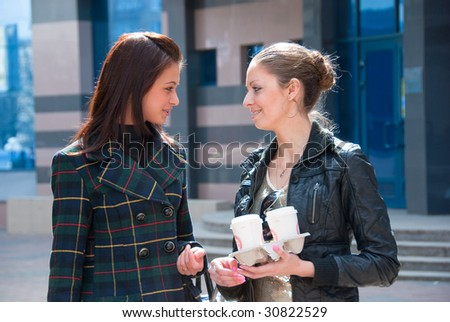 Two young girls talking on a street