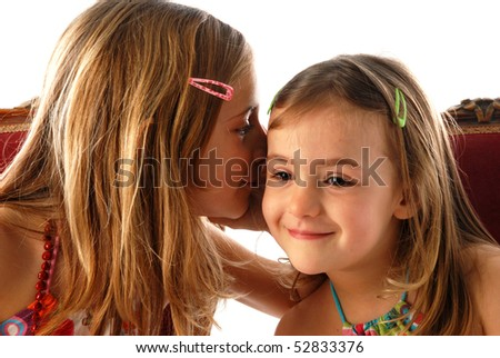 two young girls telling secrets