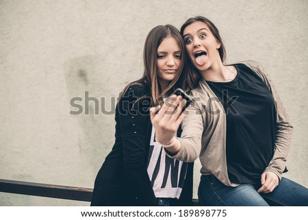 Two young girls to take pictures with your smart phone