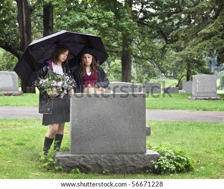 Two young girls visiting a grave site in the rain.  They hold an umbrella, a bouquet of flowers and a teddy bear. - stock photo