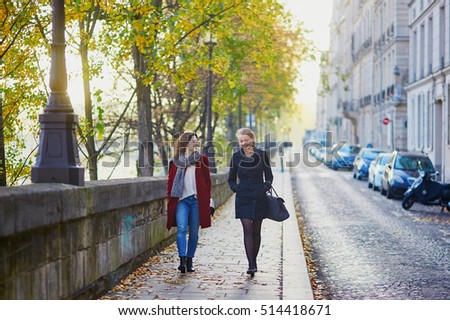Two young girls walking together in Paris on a sunny fall day. Tourism or friendship concept